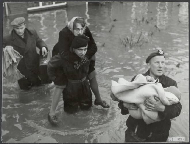 Watersnoodramp 1953. Rilland-Bath: militairen evacueren  een gezin met een baby …
